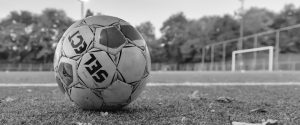 soccer ball on grass field in grayscale photography